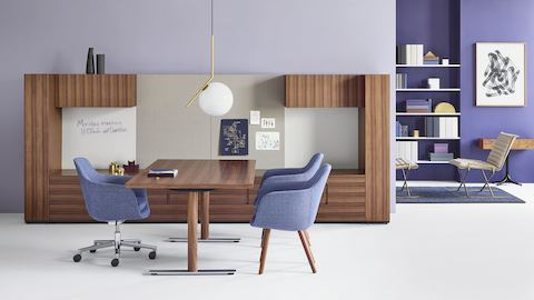 A private office featuring Geiger Rhythm Casegoods with a freestanding desk and a wall of base, overhead, and vertical storage, all in a medium wood finish.