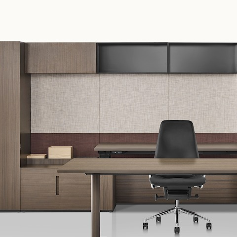 Partial view of a private office with two work surfaces and a Taper executive chair. Select to go to the Geiger Rhythm Casegoods product page.