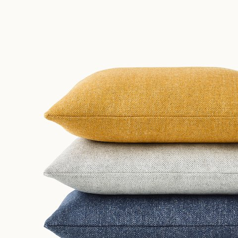 Partial view of a stack of three accent pillows in yellow, light gray, and blue fabric. Select to go to the Geiger Textiles Pillows product page.