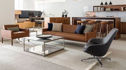An open office space featuring a sitting area that includes Wood Base Lounge Seating and an H Frame coffee table with stone upper and lower surfaces.