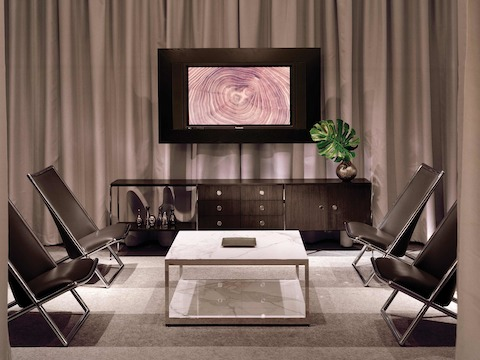 A lounge area featuring an H Frame coffee table with stone surfaces, a coordinating H Frame credenza, and four black leather Scissor Chairs.