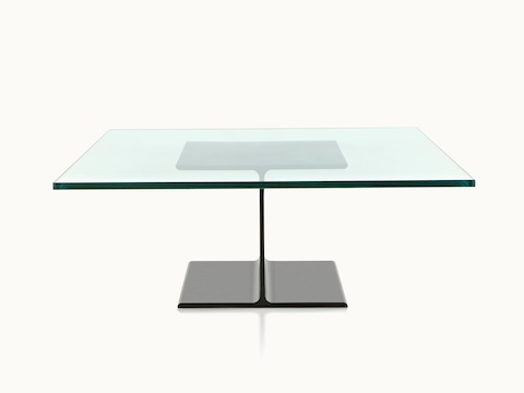 A glass-top I Beam coffee table, with the upper and lower flanges of the cast-aluminum pedestal viewed in profile.
