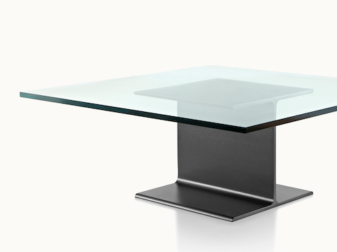 Partial angled view of a square I Beam coffee table with a glass top and black cast-aluminum pedestal.