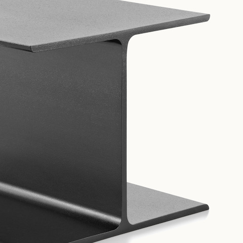 Close-up of the black cast-aluminum base of an I Beam occasional table.