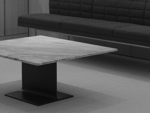 Black-and-white image of an I Beam coffee table with a marble top in an executive lounge.