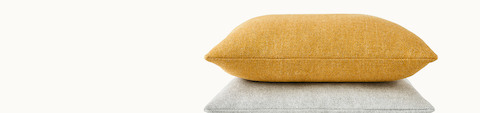 An accent pillow with gold fabric on top of another pillow with light gray fabric.