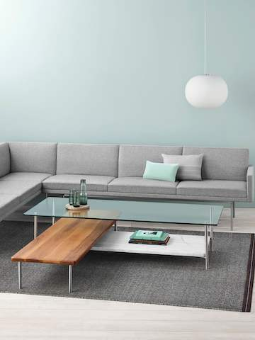 A light gray sectional borders an L-shaped Layer coffee table with three intersecting shelves of glass, wood, and marble.