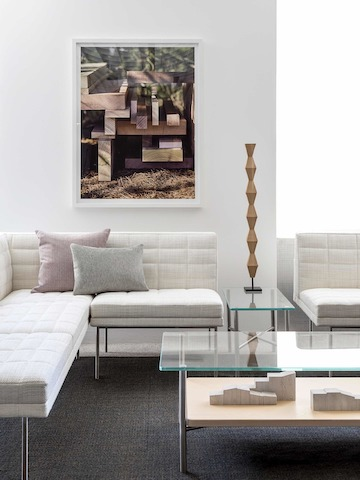 A lounge featuring a rectangular Layer coffee table with a glass top and wood shelf, complemented by off-white Tuxedo Component Lounge Seating.