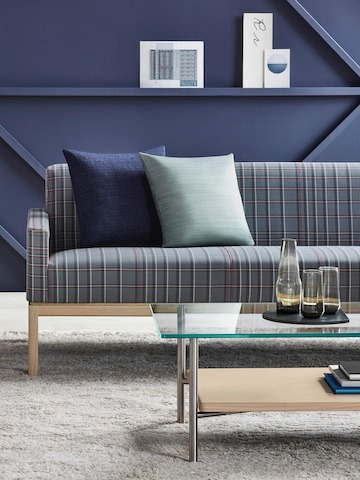 Partial view of a rectangular Layer coffee table with glass and wood shelves in front of a Wood Base Lounge Seating sofa with blue plaid fabric.