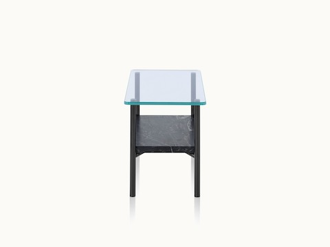 A Layer side table with a glass top and black marble lower shelf, viewed from the side.