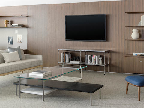 Partial view of a rectangular Layer coffee table with a glass top and lower wood drawers.