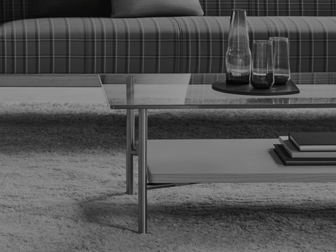 Black-and-white image showing a partial view of a rectangular Layer coffee table in front of a plaid sofa.