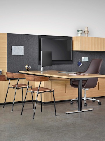 An executive office featuring Geiger Rhythm Casegoods, a peninsula desk, a brown Saiba office chair, and two Leeway side chairs.
