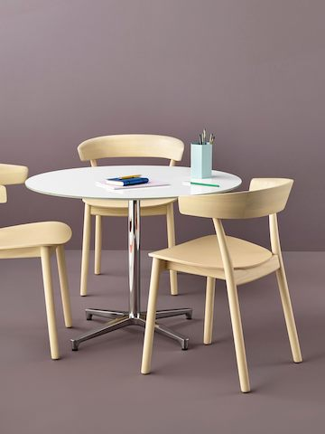 A round Saiba occasional table with a white top surrounded by three all-wood Leeway side chairs with a light finish.