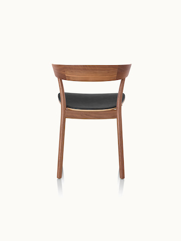 A Leeway side chair with a wood frame and backrest in a medium finish and a seat upholstered in black leather, viewed from behind.