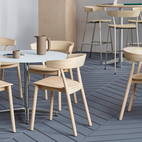 A break area featuring round tables surrounded by all-wood Leeway side chairs or Leeway Stools made of metal and wood.