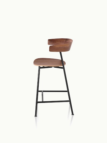 Side view of a counter-height Leeway Stool with a metal frame and a wood backrest and seat in a medium finish.
