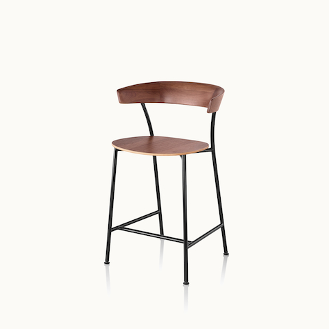 Angled view of a Leeway Stool with a black metal frame and a wood backrest and seat in a medium finish. Select to go to the Leeway Stool product page.