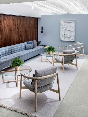 A lounge featuring three round Loophole occasional tables, a light blue Tuxedo Classic Lounge Seating sofa, and three light gray Crosshatch Chairs.