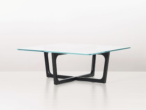 A rectangular Loophole coffee table with a 30-inch-deep glass top and black wood base, viewed at an angle.