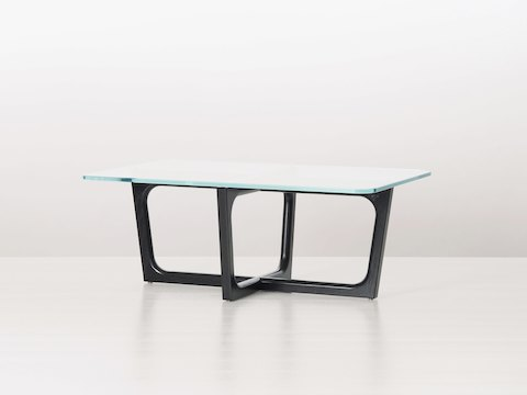 A rectangular Loophole coffee table with a 24-inch-deep glass top and black wood base, viewed at an angle.