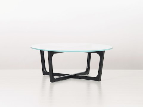 A round Loophole coffee table with a glass top and black wood base.