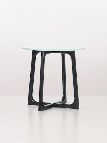 A round Loophole side table with a glass top and black wood base.