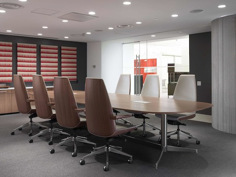 An enclosed meeting room featuring an MP Conference Table surrounded by high-back Clamshell Lounge Chairs with leather upholstery.