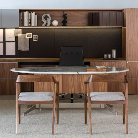 An executive office featuring an oval MP Height-Adjustable Table with a stone top used as a desk.