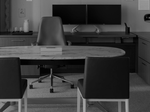 Black-and-white image of an executive office featuring an oval MP Height-Adjustable Table with a stone top used as a desk.