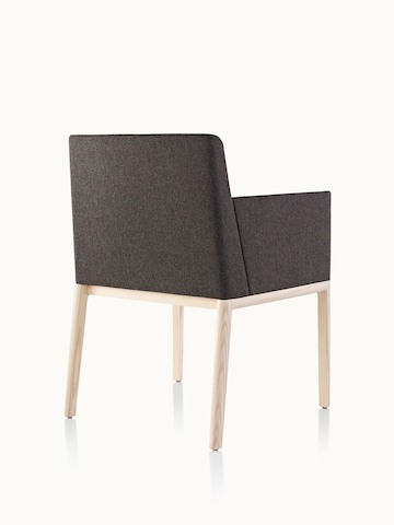 A Nessel side chair with black fabric upholstery, wraparound arms, and a wood frame with a light finish, viewed from behind at an angle.