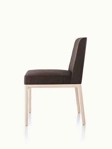 Side view of an armless Nessel side chair with black fabric upholstery and a wood frame with a light finish.