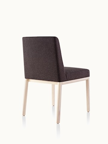 An armless Nessel side chair with black fabric upholstery and a wood frame with a light finish, viewed from behind at an angle.