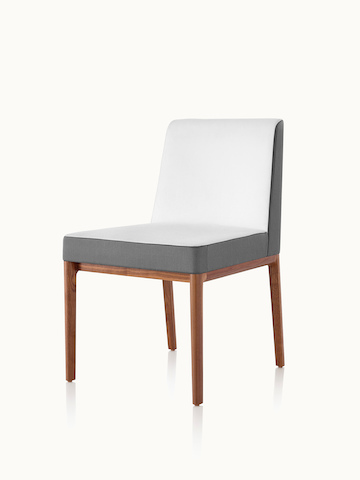Angled view of an armless Nessel side chair with two-tone upholstery in off-white and gray.