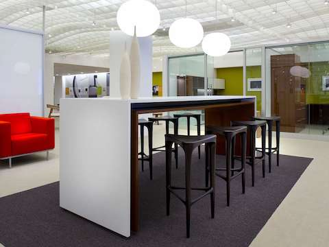 An open interaction space featuring a white Peer Table and dark brown 2 by 3 Stools to support collaboration.