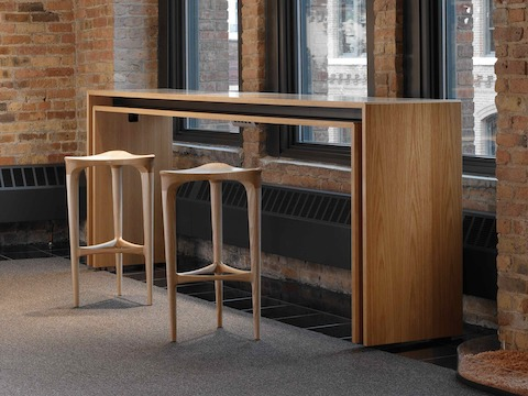 A rectangular Peer Table and a pair of complementary 2 by 3 Stools positioned against three windows in a brick-walled office space.