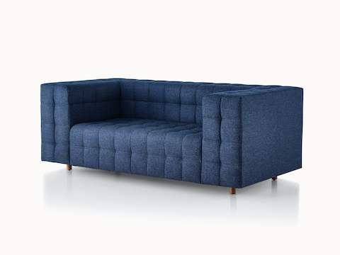 A two-seat Rapport Sofa in a deep navy colored textile, viewed at an angle.