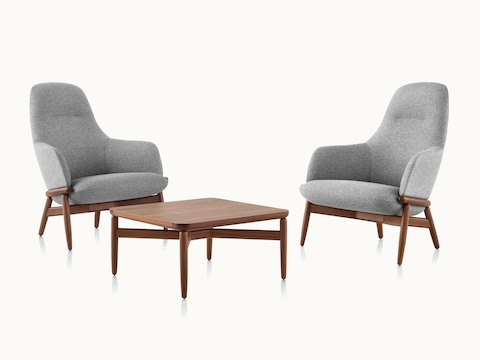 Two high-back Reframe lounge chairs with light gray upholstery on either side of a Reframe occasional table with a medium finish.