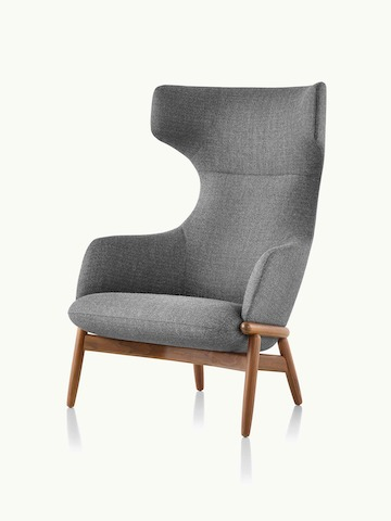 Angled view of a wing-back Reframe lounge chair with dark gray upholstery and a wood frame in a medium finish.