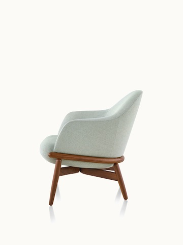 Side view of a mid-back Reframe lounge chair with light green upholstery and a wood frame in a medium finish.