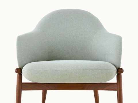 The upper half of a mid-back Reframe lounge chair with light green upholstery, viewed from the front.