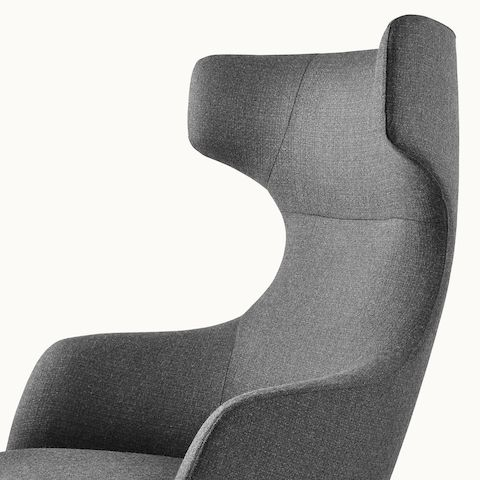 Side view of a wingback Reframe lounge chair with dark gray upholstery.