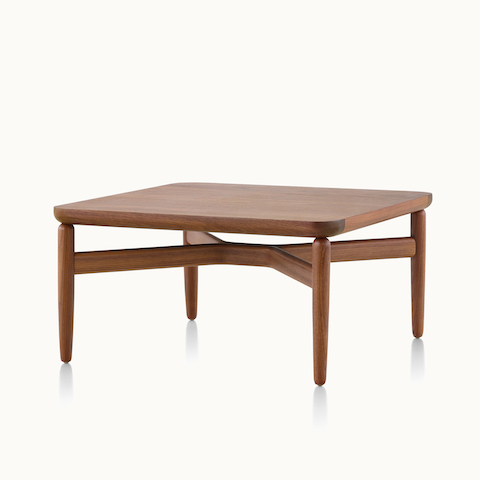 Angled view of a rectangular Reframe occasional table with a medium wood finish. Select to go to the Reframe Tables product page.