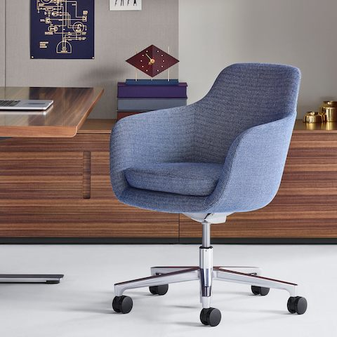 A private office featuring a mid-back Saiba office chair with light blue upholstery, a height-adjustable base, and casters.