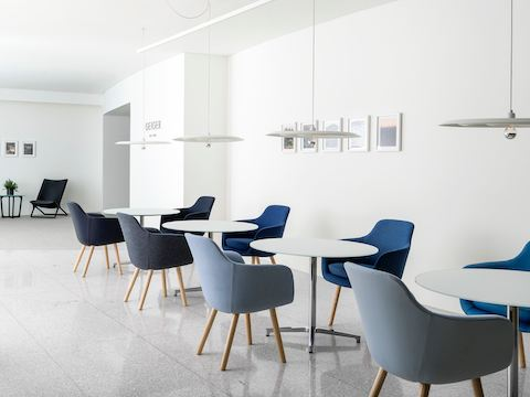 An informal meeting space featuring round Saiba occasional tables with Saiba Side Chairs upholstered in various shades of blue.