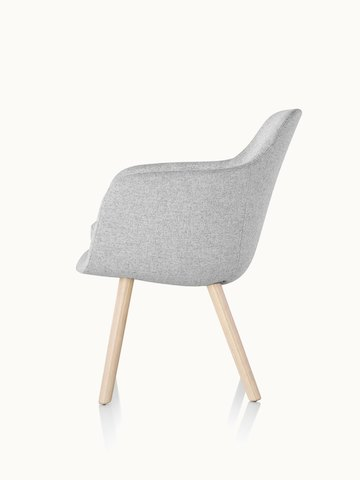 Side view of a Saiba Side Chair with light gray upholstery and wood legs in a light finish.