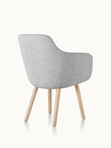 A Saiba Side Chair with light gray upholstery and wood legs in a light finish, viewed from behind at an angle.