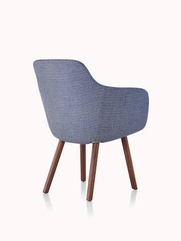 A Saiba Side Chair with blue upholstery and wood legs in a medium finish, viewed from behind at an angle.