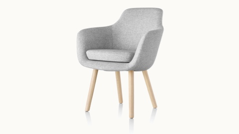 Angled view of a Saiba Side Chair with light gray upholstery and wood legs in a light finish.