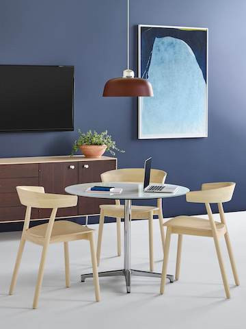 Three Leeway side chairs with a light wood finish complement a round Saiba occasional table with a white top and aluminum pedestal base.